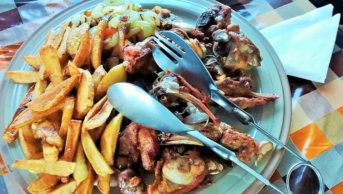Cabrito frito con cabeza de ajo asada y papas de Lanzarote.
